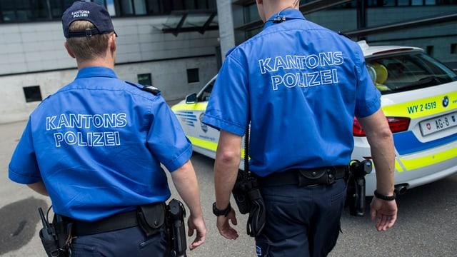 Polizisten laufen neben Streifenwagen vorbei
