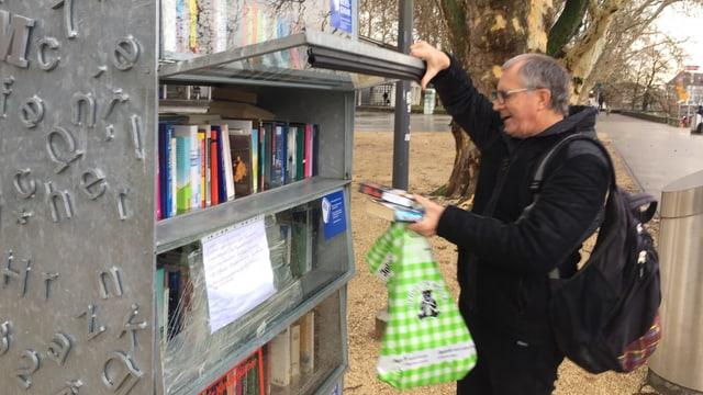 Mann mit Rucksack und Bücher in der Hand hebt Tür eines Regals auf.