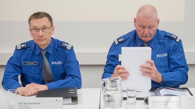 Zwei Polizisten anlässlich einer Medienkonferenz sitzen an einem Tisch.