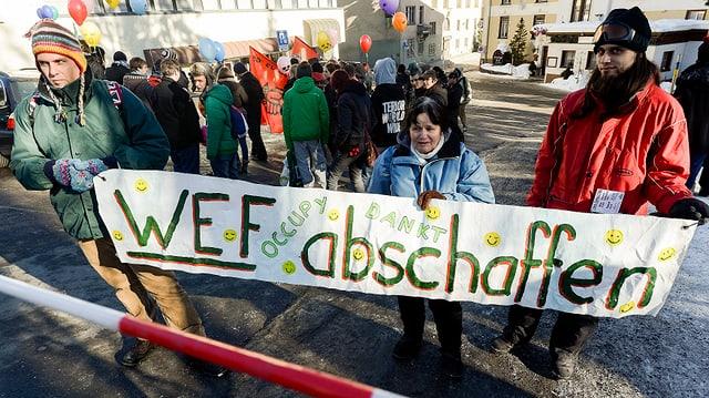 Demonstranten halten ein Transparent hoch. Darauf steht: «WEF abschaffen».