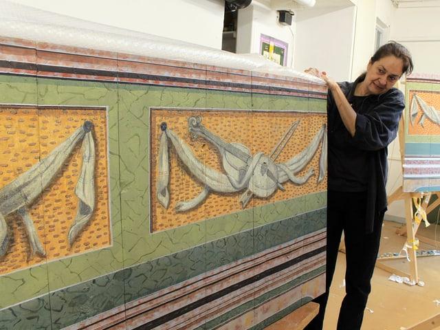 Brigitta Berndt zeigt eine der fertig restaurierten Malereien.