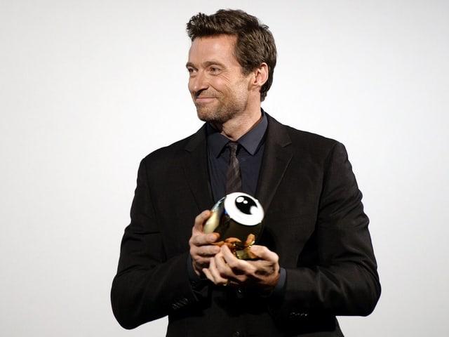 Hugh Jackman im schwarzen Anzug vor weisser Wand mit einem Award in Form eines Auges