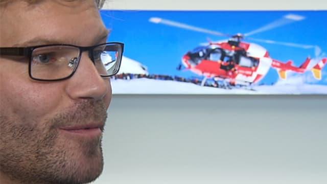 Hardegger im Seitenporträt. Im Hintergrund ein Foto eines Helikopters.