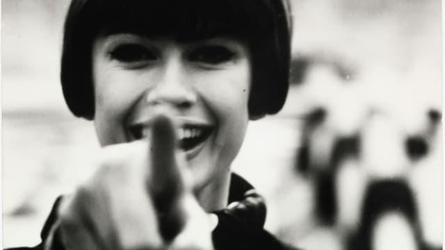 Eine Frau zeigt mit dem Finger in die Kamera.