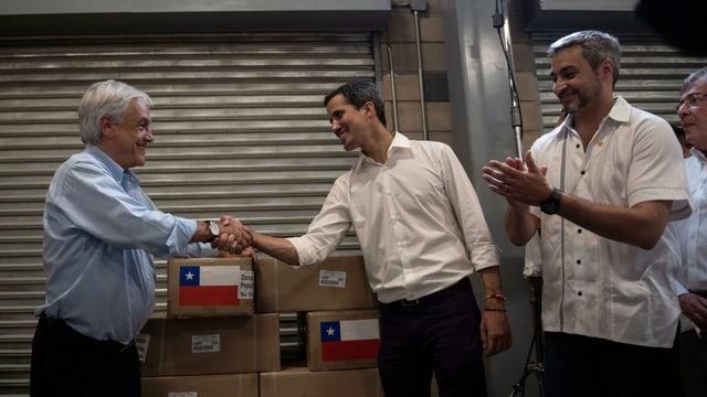 Drei Männer, zwei davon begrüssen sich per Handschlag.