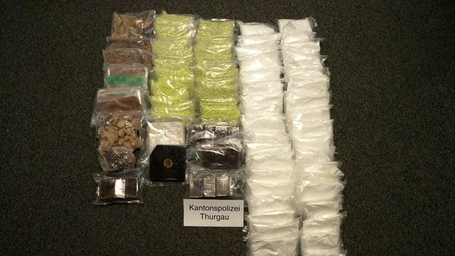 Zwei Dutzend Päckchen Drogen in verschiedenen Farben aufgereiht.