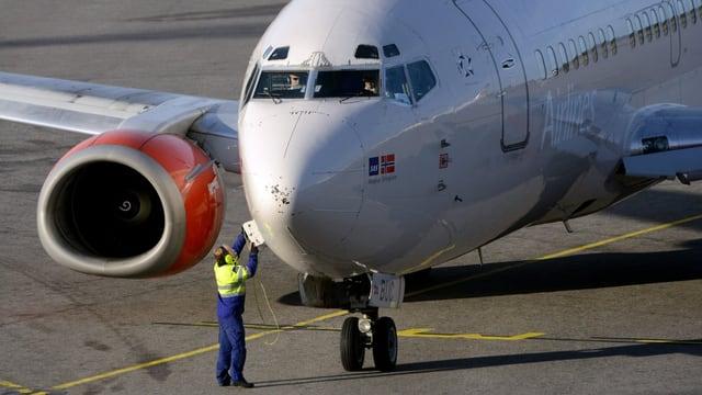 Ein Flugzeug am Boden, ein Techniker öffnet eine Klappe beim Bug.