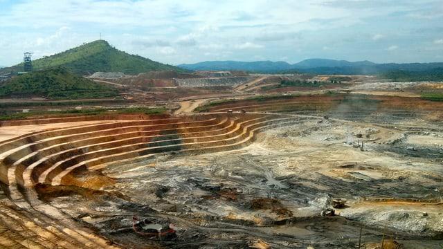 Symbolbild: Grossflächige Tagbau-Mine mit schwerem Gerät am Minenboden.