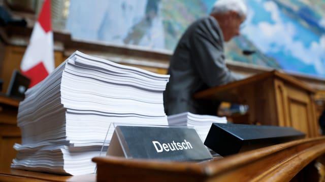 Stapel mit Papieren auf Deutsch im Nationalratssaal.