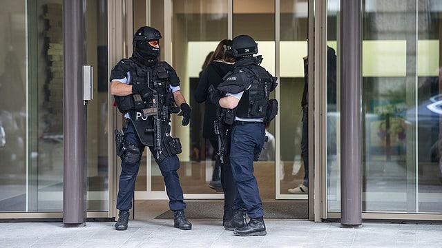 Zwei Polizisten in Kampfmontur sichern den Eingang des Verlagshauses.
