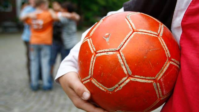 Kind mit Fussball unterm Arm.