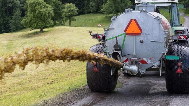 Traktor zieht Güllefass und schiesst Gülle auf Feld
