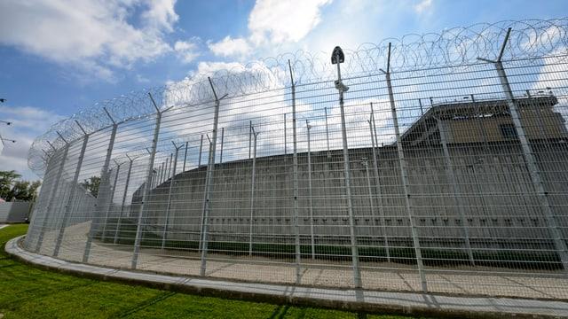 Gefängnis von ausssen mit hohen Stacheldrahtzaun vor leicht bewölktem, aber blauem Himmel.