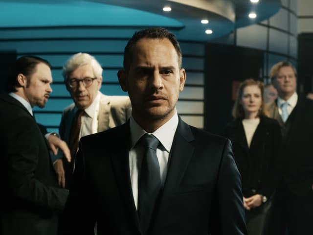 Ein Mann mit Anzug schaut besorgt in die Kamera.