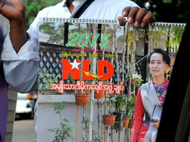 Mann hält Wahlplakat in der Hand.