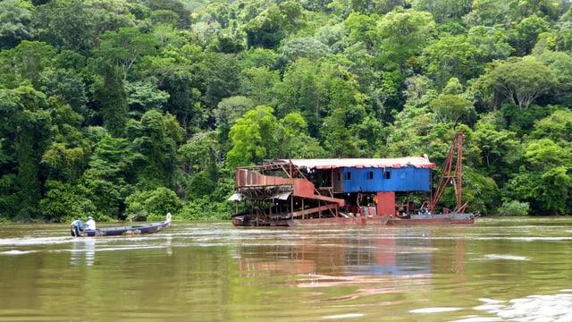 Eine Goldschürfanlage: eine blaue Wellblech-Hütte auf dem Wasser.