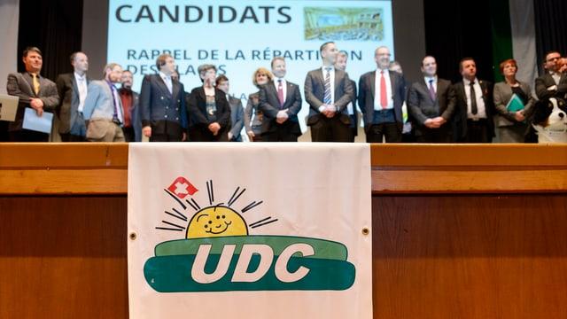 Das Parteilogo der SVP. Im Hintergrund die Waadtländer Nationalratskandidaten.