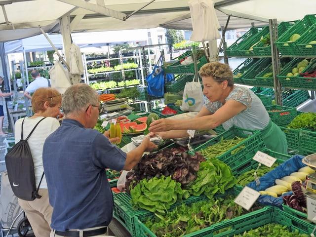 Marktstand mit Salaten und anderem Gemüse, Leute kaufen ein.