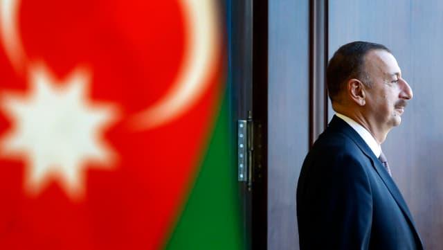 Präsident Alijev von der Seite vor einer Fahne Aserbaidschans.