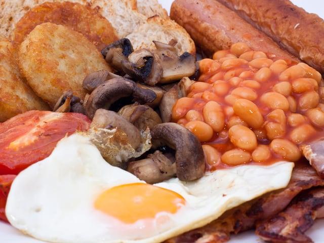 Nahaufnahme eines Tellers mit Bohnen, Würsten, Tomaten, Speck, Pilzen, Eiern, Kartoffeln und Toast.