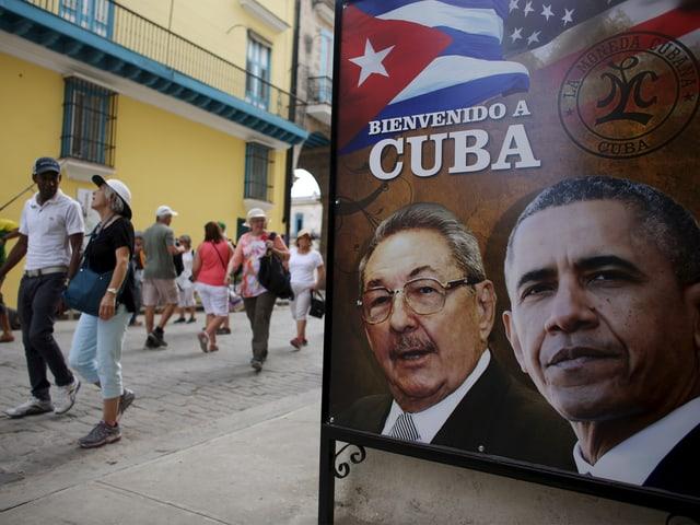 """Im Vordergrund ein Plakat, das Barack Obama zusammen mit Kubas Präsident Raul Castro zeigt, dazu die Aufschrift """"Willkomen auf Kuba"""""""