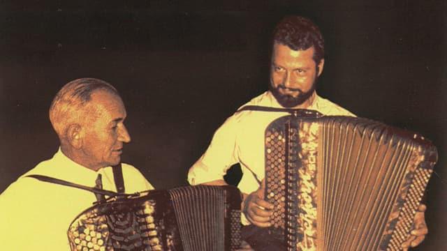 Die beiden Musiker spielen sitzend auf dem Akkordeon.