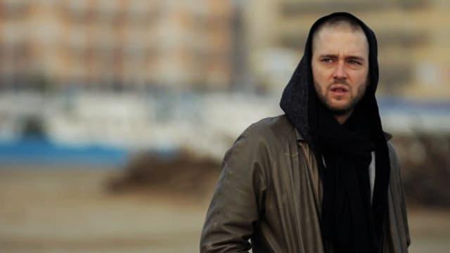 Ein Mann mit Lederjacke und Kaputzenpulli.