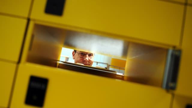 Blick durch ein Postfach hindurch, dahinter ein Pöstler.