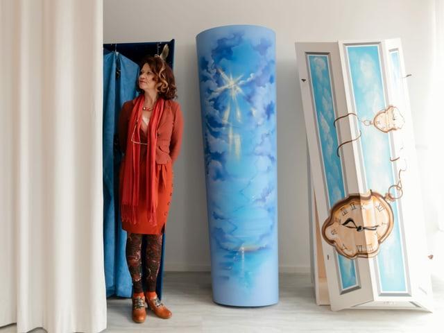 Eine Frau steht neben zwei bunten Särgen.