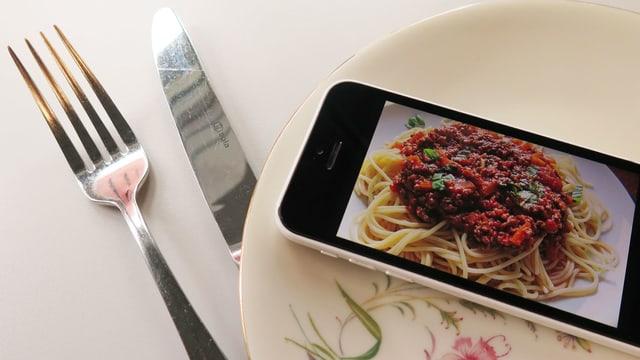 Messer, Gabel und ein Teller. Auf dem Teller ist ein Smartphone mit einem Bild von Spaghetti Bolognese.