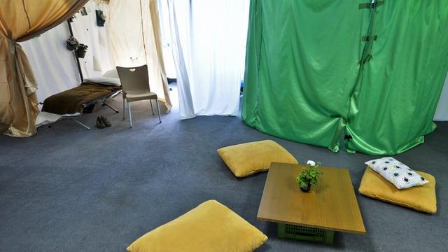 Eine provisorische Unterkunft mit Sitzkisten auf dem Boden und einem Bett in der Ecke.