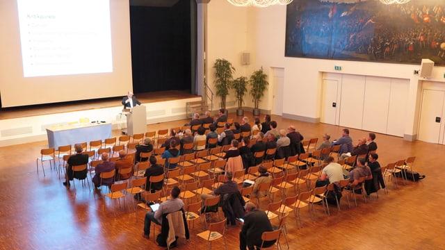 In einem Saal doziert ein Mann vor einer beleuchteten Leinwand, einige Zuhörer sitzen auf Stühlen. Viele Sitze bleiben aber leer.