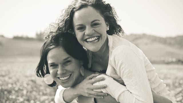 Zwei junge Frauen, die eine trägt die andere auf dem Rücken.