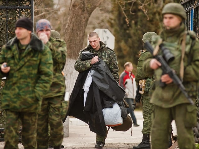 Soldaten ohne Erkennungszeichen auf der Krim, dahinter entwaffneter ukrainischer Soldat