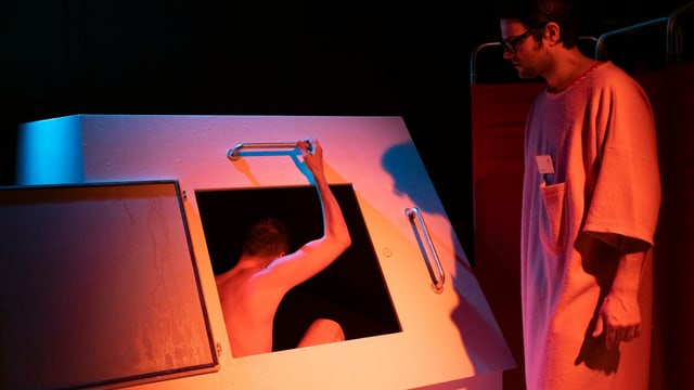 Ein Theaterbesucher steigt nackt in einen Kasten.