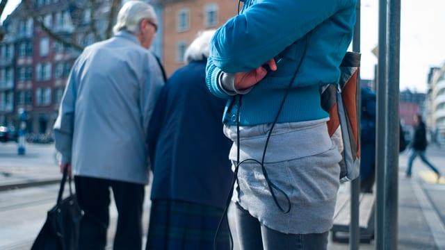 Junge Frau wartet auf das Tram, während zwei alte Frauen vorbeigehen.