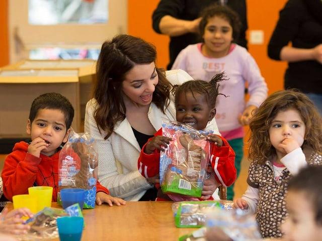 Laetitia Guarino an einem Tisch sitzend und von Kindern umgeben.