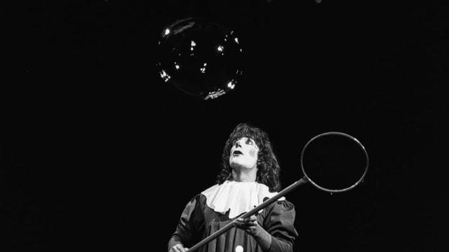 ein schwarz-weiss Foto eines Clowns mit Seifenblase