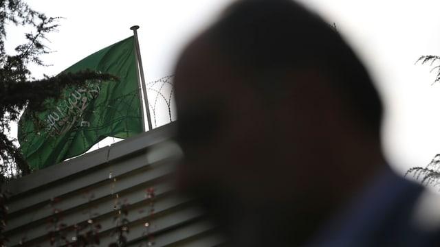 Silhouette eines Mannes vor einem Gebäude. Darauf weht die Flagge Saudi-Arabiens.