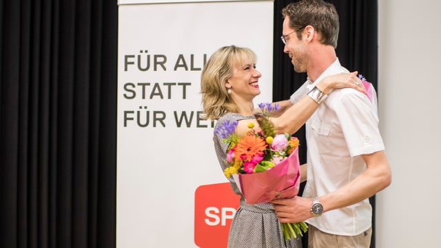 Frau und Mann mit Blumenstrauss umarmen sich, im HiGru SP-Plakat