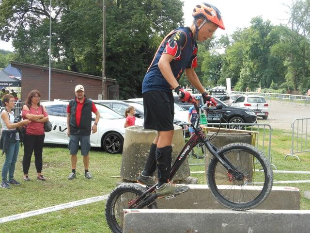 Ein Jugendlichen balanciert mit seinem Mountainbike auf einer Steinmauer.