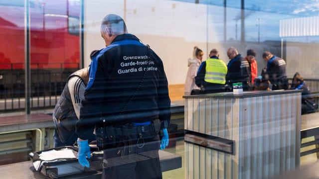 Ein Grenzbeamter kontrolliert die Personen.