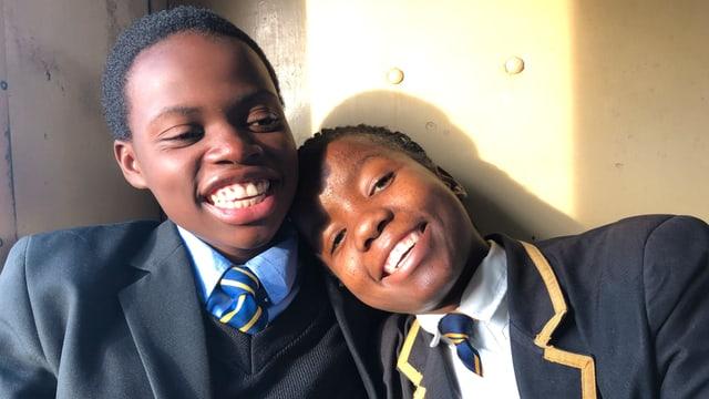 Zwei junge Mädchen in Schuluniform schauen lachend in die Kamera.