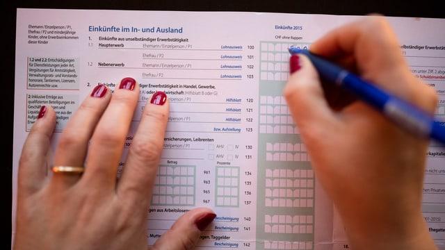 zwei Hände mit Kugeli auf Steuerformular