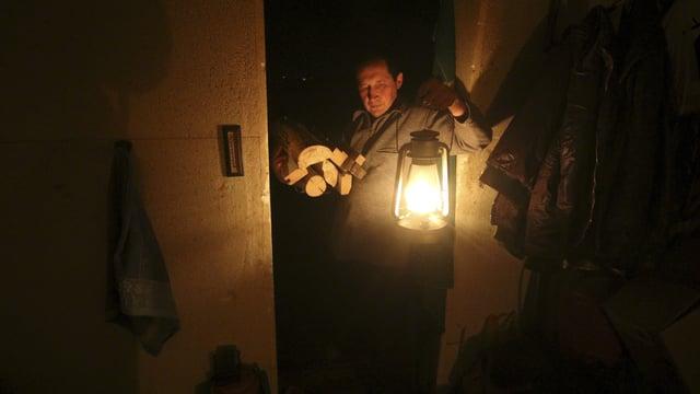 Ein Mann beleuchtet sein Heim mit einer Öllampe und trägt Brennholz unter dem Arm.