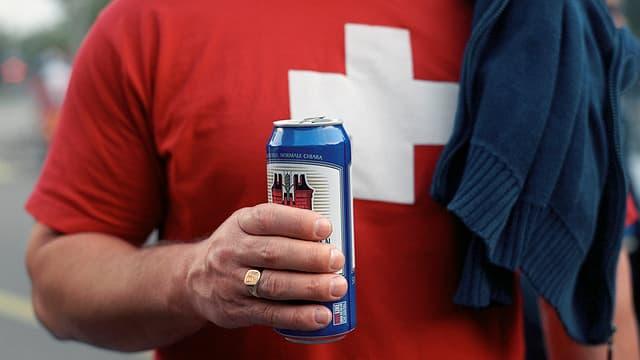 Fussballfan mit Schweizerkreuz auf T-Shirt und Bierdose.