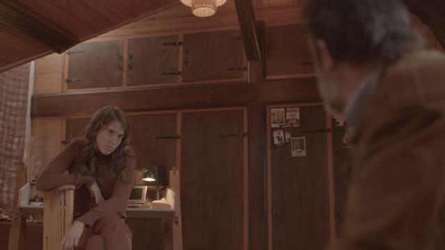 Eine Frau sitzt auf einem Stuhl und blickt einen Mann an.