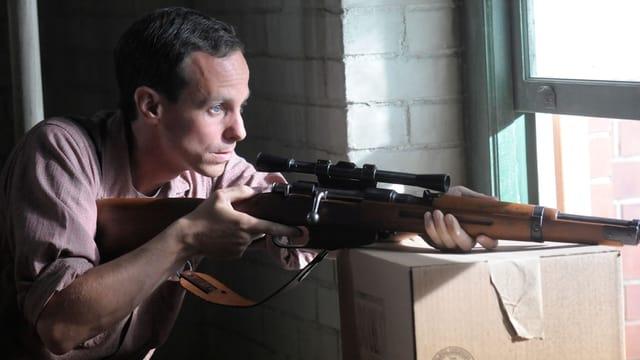 Ein Mann zielt mit einem Scharfschützengewehr aus dem Fenster.