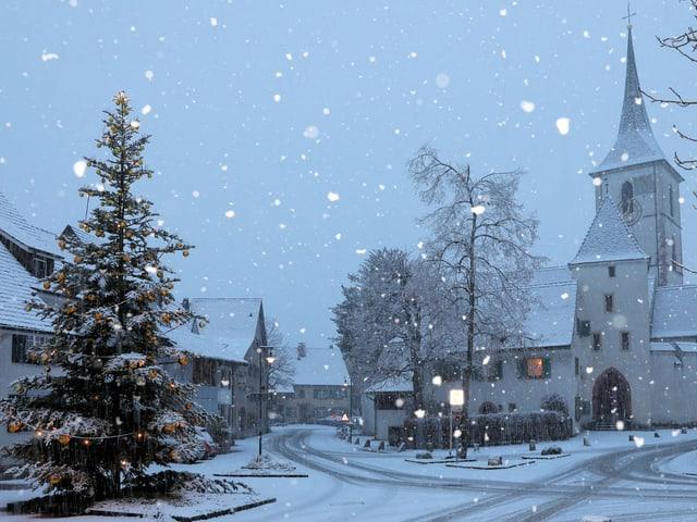 Dorfplatz mit verschneitem Weihnachtsbaum und Kirche