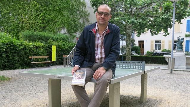 Raphael Zehnder auf einem Pingpong-Tisch mit seinem Buch
